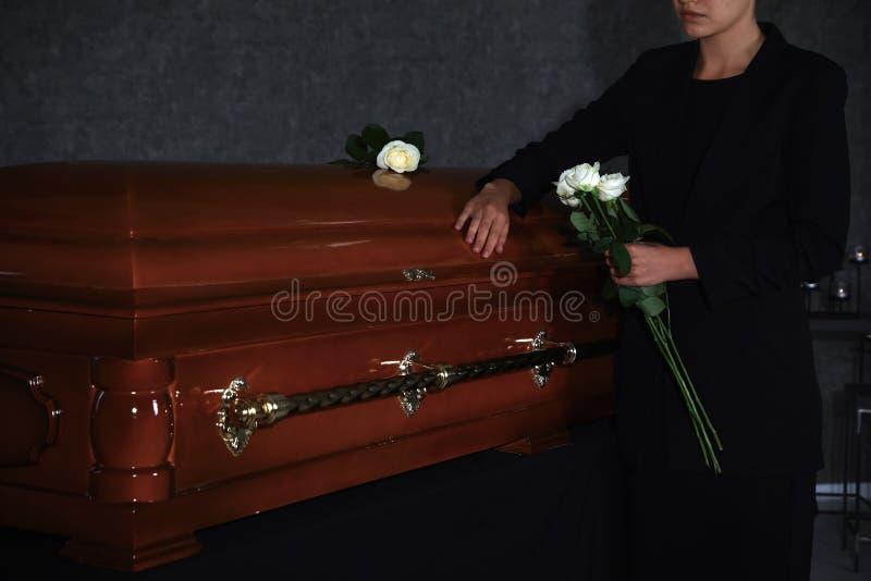 Jonge vrouw met witte rozen dichtbij kist in rouwkamer, stock foto