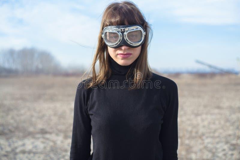 Jonge vrouw met zandbeschermende brillen die zich alleen bevinden stock foto's