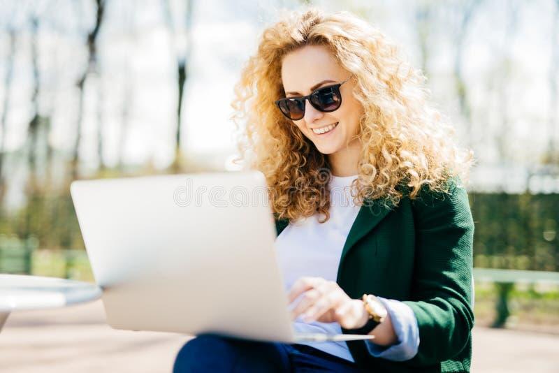 Jonge vrouw met zonnebril die pluizig haar hebben die vreugdevol het rusten in park glimlachen die Internet doorbladeren die lapt stock afbeelding