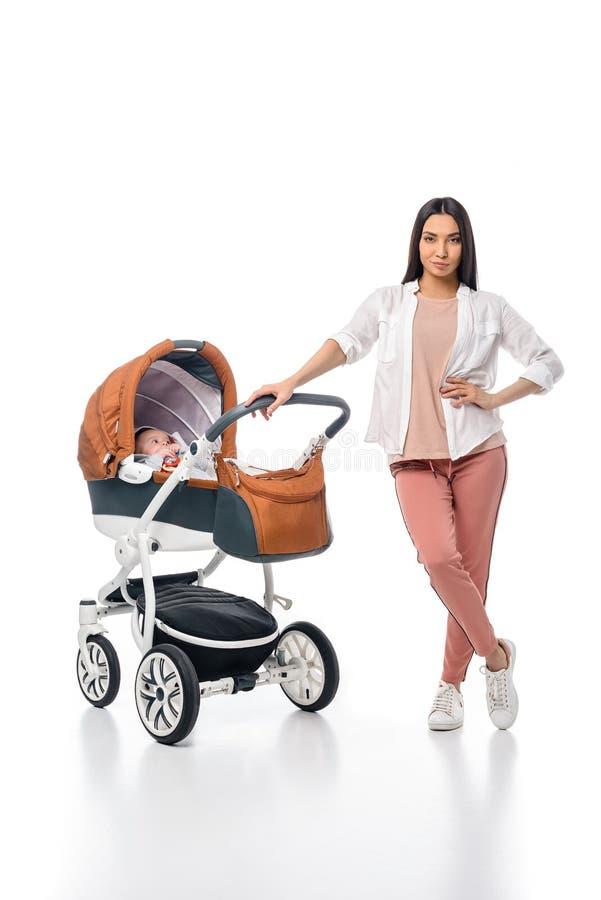 jonge vrouw met zuigelingsbaby in kinderwagen royalty-vrije stock afbeeldingen