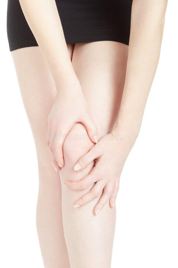 Jonge vrouw met zwarte rok die aan kniepijn lijden stock afbeelding
