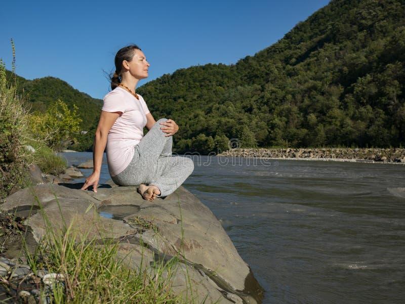 Jonge vrouw oefent yoga uit in de Half Lord of the Fishes Pose Matsyendra pose in het bergmeer royalty-vrije stock fotografie