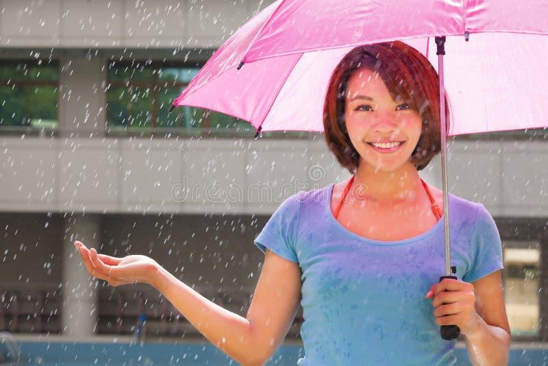 Jonge vrouw onder roze paraplu stock foto