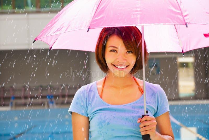 Jonge vrouw onder roze paraplu stock afbeelding