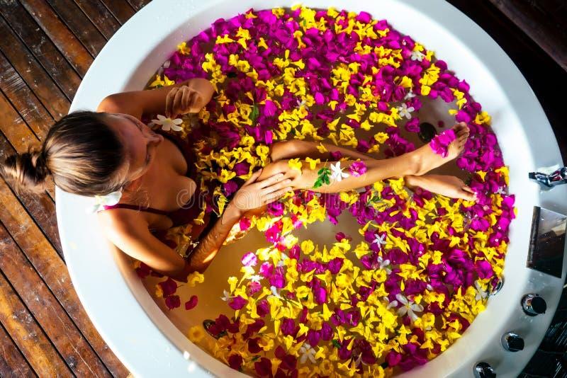 Jonge vrouw ontspannen in bloembad, organische huidverzorging, luxe spa hotel Bovenaanzicht van schoonheidslichaamsverzorging uit stock fotografie
