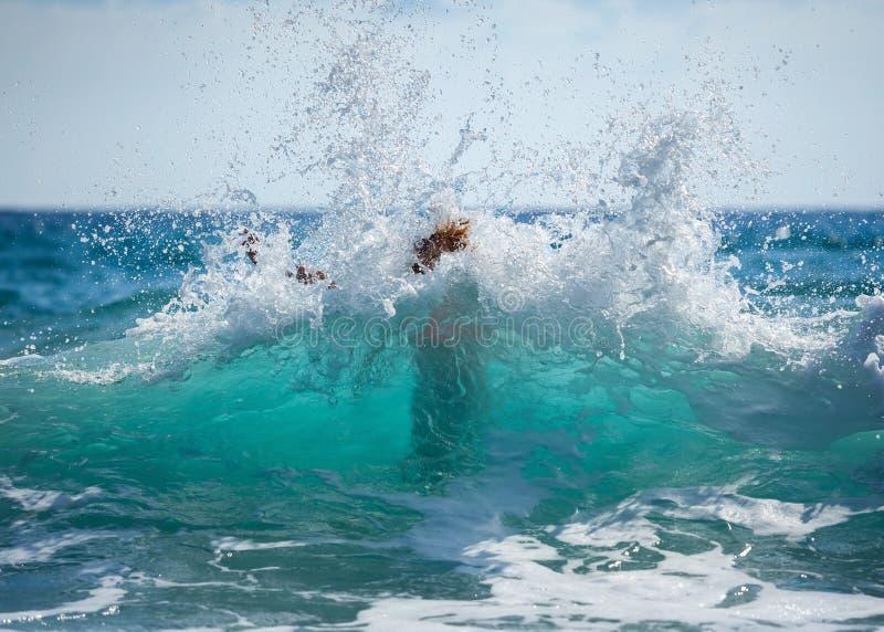 Jonge vrouw in onverwachte bikini overstroomd met grote golf royalty-vrije stock foto