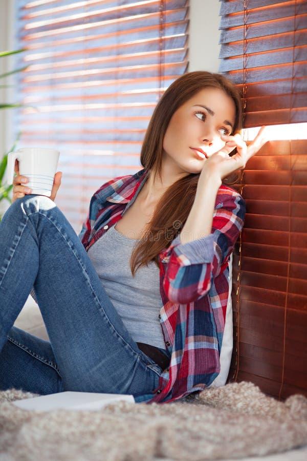 Jonge vrouw op bank thuis royalty-vrije stock afbeeldingen