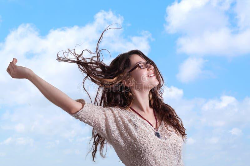 Jonge vrouw op blauwe hemelachtergrond stock fotografie