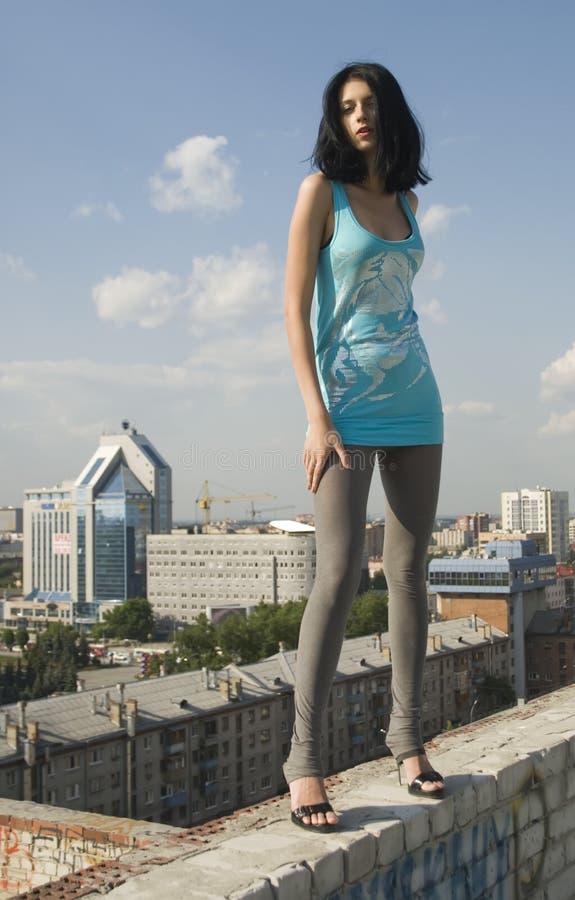 Jonge vrouw op dak stock afbeelding