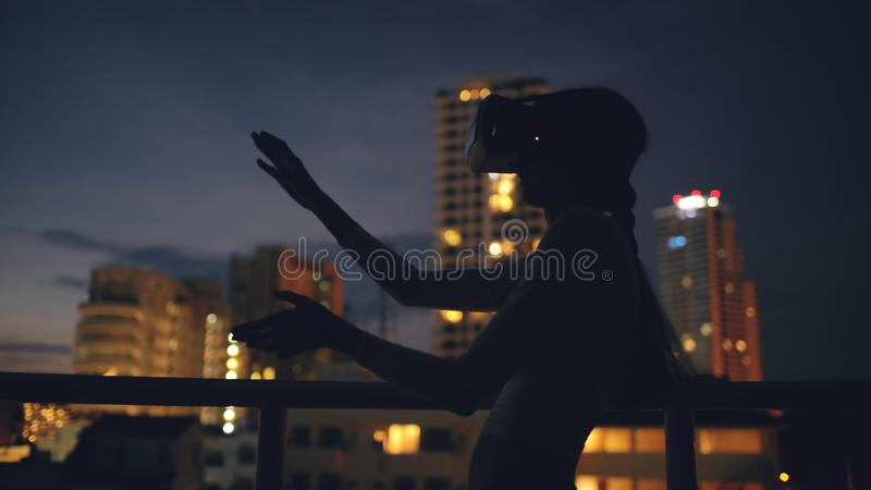 Jonge vrouw op dakterras gebruikend virtuele werkelijkheidshoofdtelefoon en hebbend VR-ervaring bij nacht stock fotografie