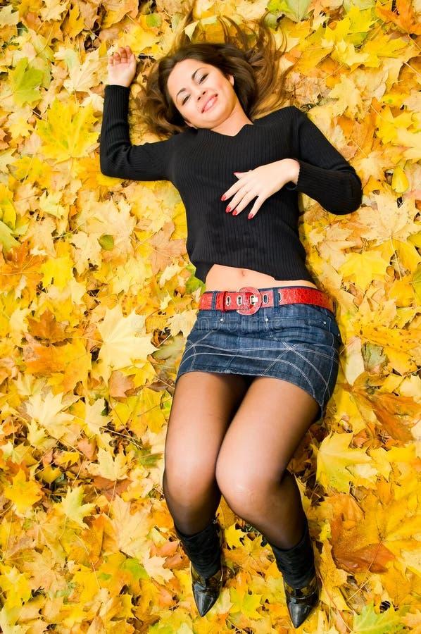 Jonge vrouw op de herfstbladeren stock afbeelding