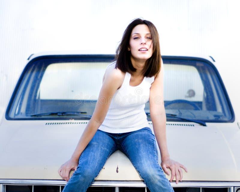 Jonge vrouw op de kap van oude vrachtwagen royalty-vrije stock fotografie
