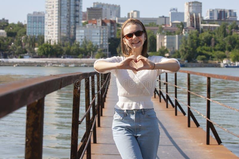Jonge vrouw op de pijler bij de rivier stock foto