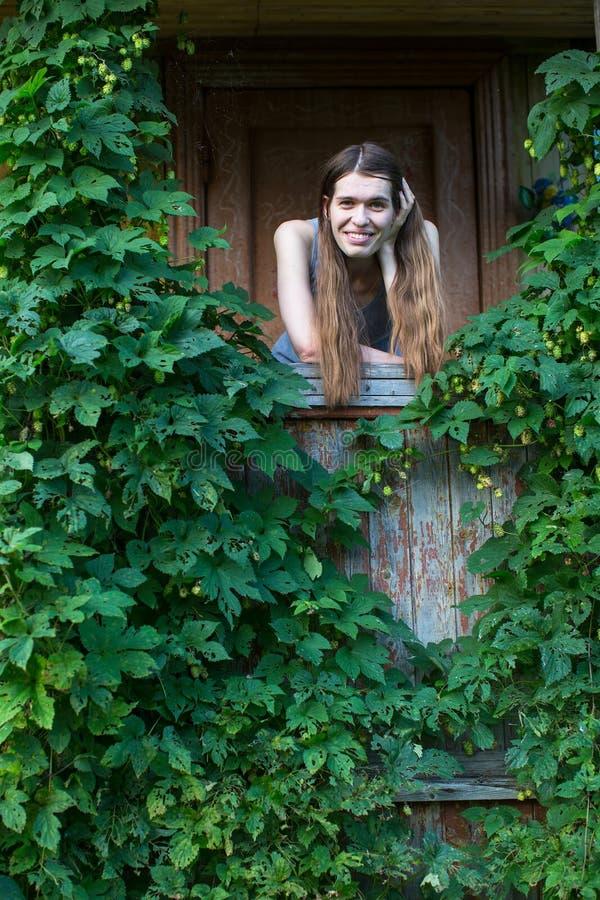 Jonge vrouw op de portiek van een dorpshuis onder groen stock fotografie