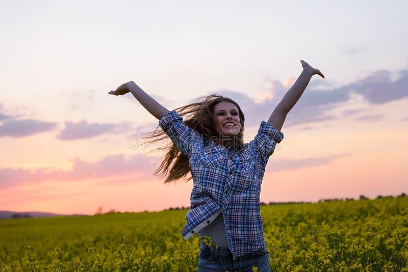 Jonge vrouw op een gebied van olieraapzaad in bloei in zonsondergang Vrijheid en ecologieconcept stock fotografie