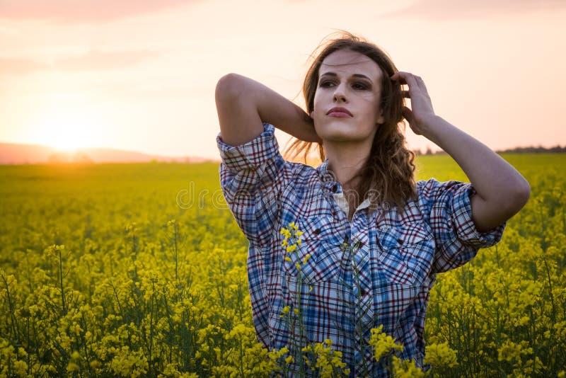 Jonge vrouw op een gebied van olieraapzaad in bloei in zonsondergang Vrijheid en ecologieconcept royalty-vrije stock afbeeldingen