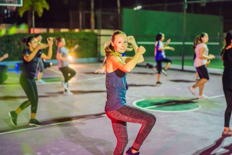 Jonge vrouw op een groepstraining op het basketbalhof in de avond royalty-vrije stock foto's