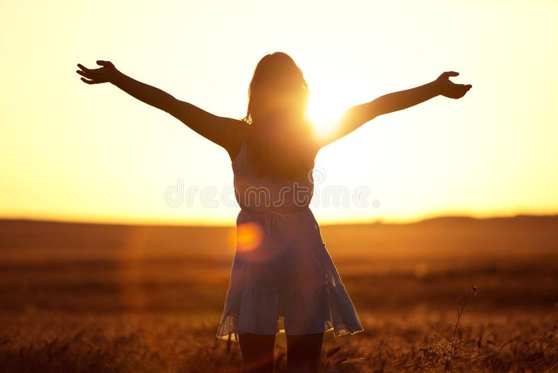 Jonge vrouw op gebied onder zonsonderganglicht stock foto