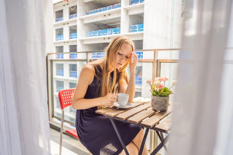 Jonge vrouw op het balkon dat door de de bouwwerken buiten wordt geërgerd Lawaaiconcept Luchtvervuiling door de bouw van stof stock afbeelding