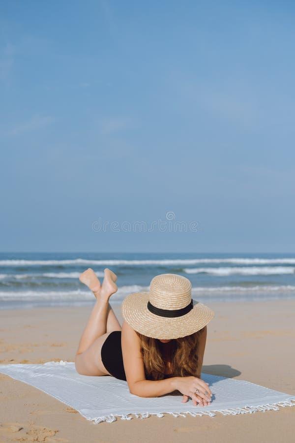 Jonge vrouw op het strand dichtbij de oceaan stock foto