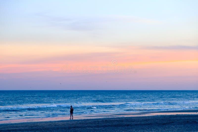 Jonge vrouw op het strand die op het overzees letten bij de zonsondergang royalty-vrije stock afbeelding