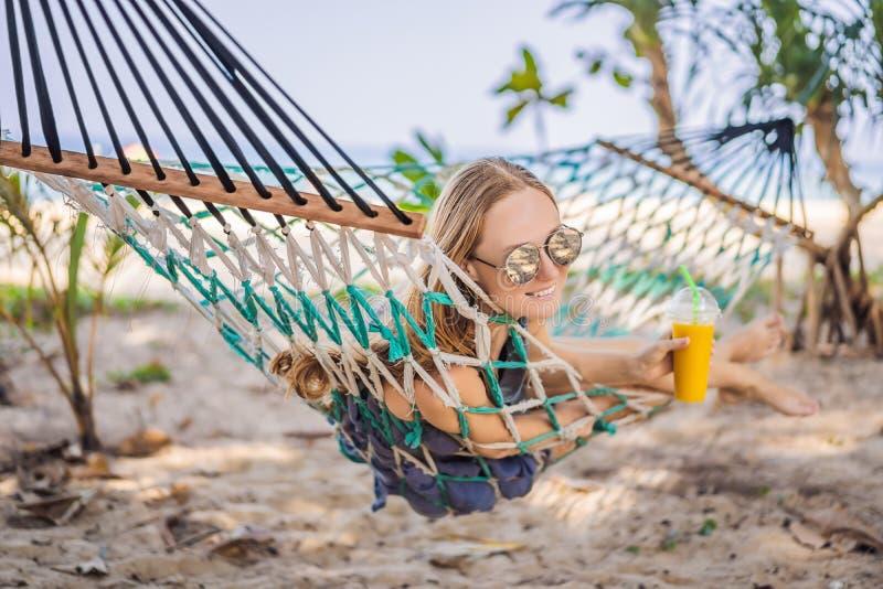Jonge vrouw op het strand in een hangmat met een drank royalty-vrije stock afbeeldingen