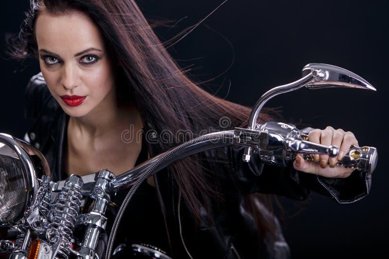 Jonge vrouw op motorfiets stock foto's