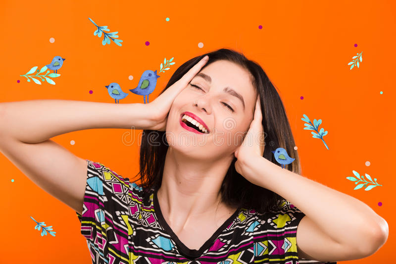 Jonge vrouw op oranje achtergrond met blauwe vogels stock afbeeldingen