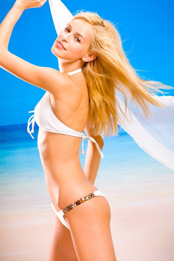 Jonge vrouw op overzees strand stock foto's