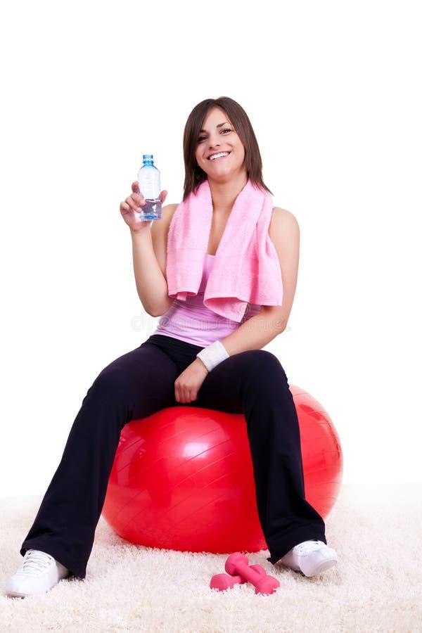 Jonge vrouw op rode geschiktheidsbal stock foto