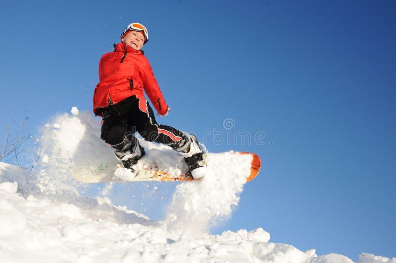Jonge vrouw op snowboard het springen stock afbeelding