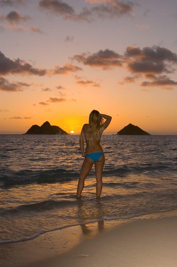 Jonge vrouw op strand bij zonsopgang royalty-vrije stock foto