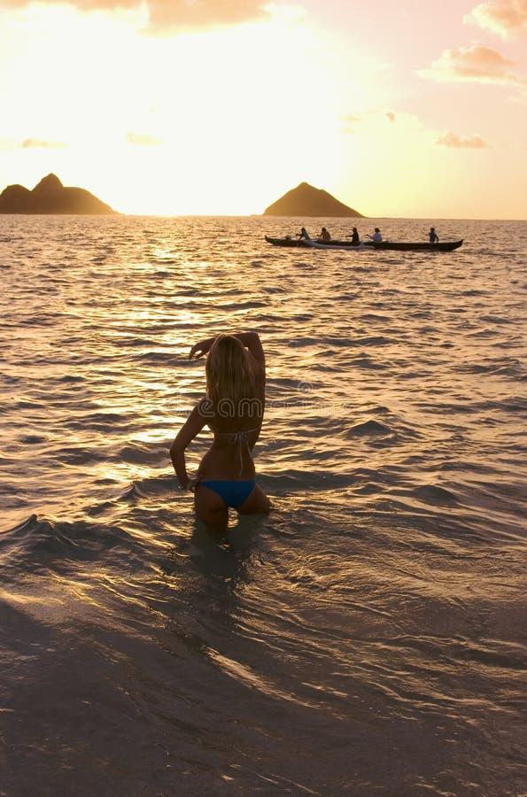 Jonge vrouw op strand bij zonsopgang royalty-vrije stock foto's