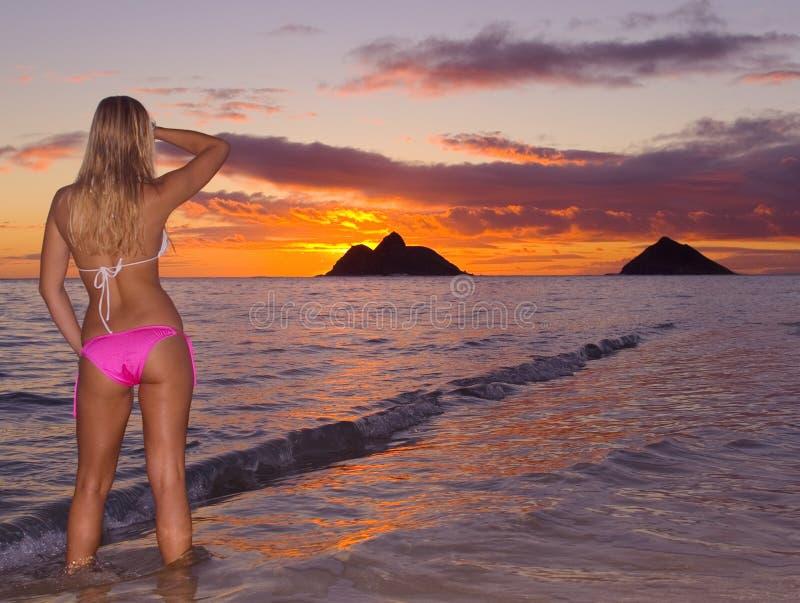 Jonge vrouw op strand bij zonsopgang royalty-vrije stock fotografie
