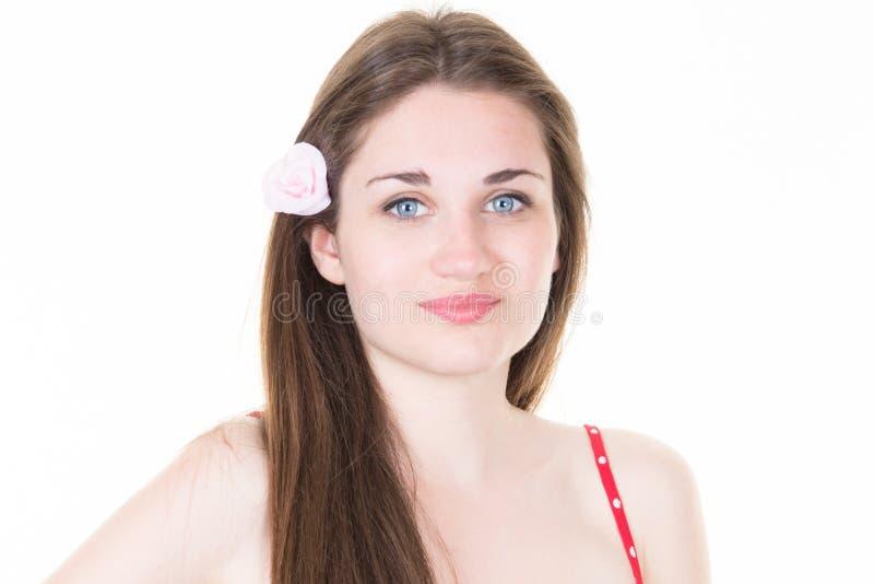 Jonge vrouw op witte achtergrond met bloem in hoofd stock afbeeldingen
