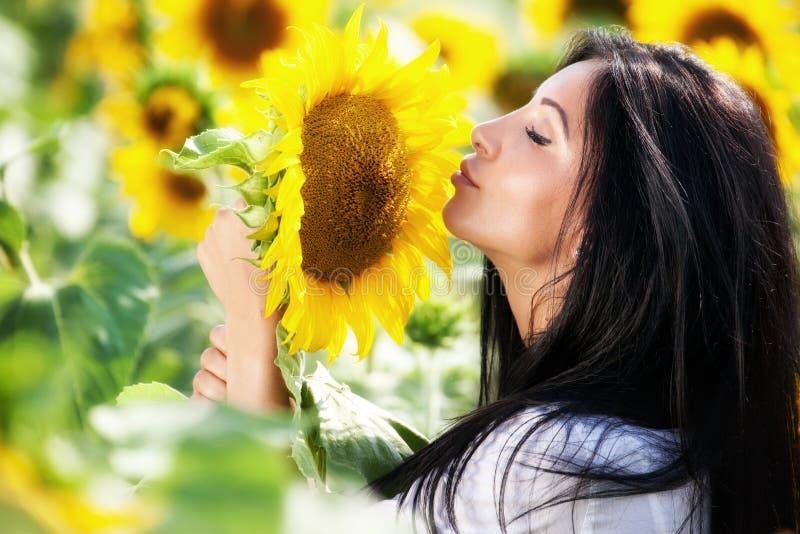 Jonge vrouw op zonnebloemgebied royalty-vrije stock afbeeldingen