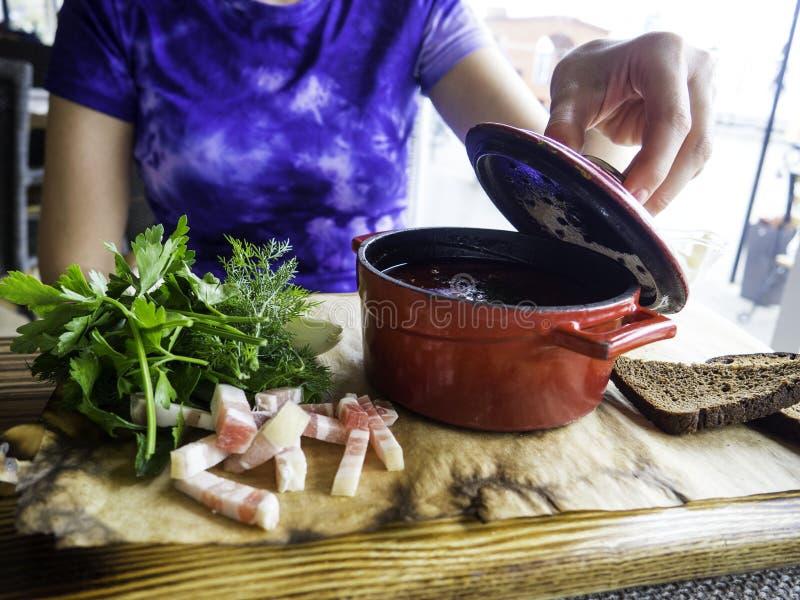 Jonge vrouw opent borscht pot deksel Traditionele Russische bietensoep Ruw en vegan met tomaten, aardappelen, reuzel, zure royalty-vrije stock foto's