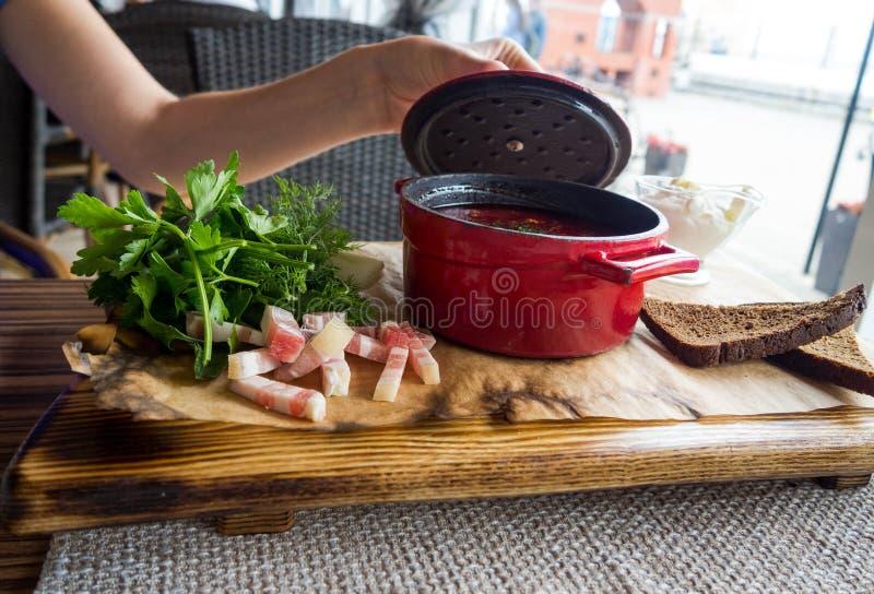 Jonge vrouw opent borscht pot deksel Traditionele Russische bietensoep Ruw en vegan met tomaten, aardappelen, reuzel, zure royalty-vrije stock afbeeldingen