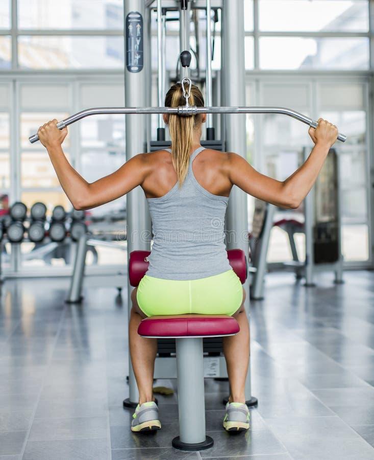 Jonge vrouw opleiding in de gymnastiek royalty-vrije stock afbeelding