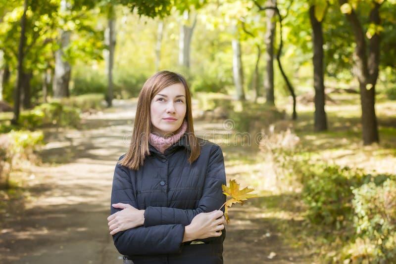 Jonge vrouw in park die, eenzaam, over iets denken royalty-vrije stock afbeeldingen