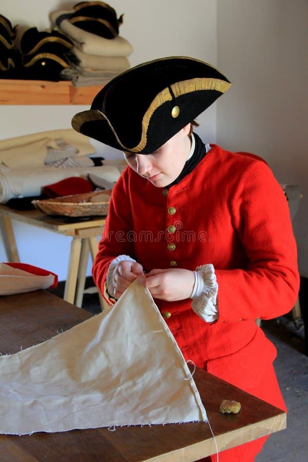Jonge vrouw in periodekleding als kleermaker, Fort Ticonderoga, New York, 2015 stock foto