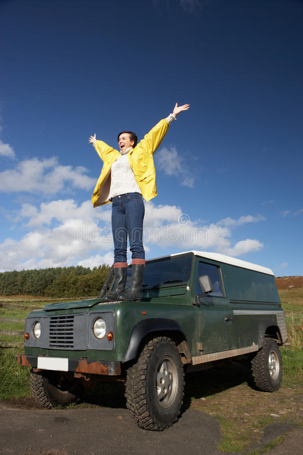 Jonge vrouw in platteland met SUV stock afbeelding
