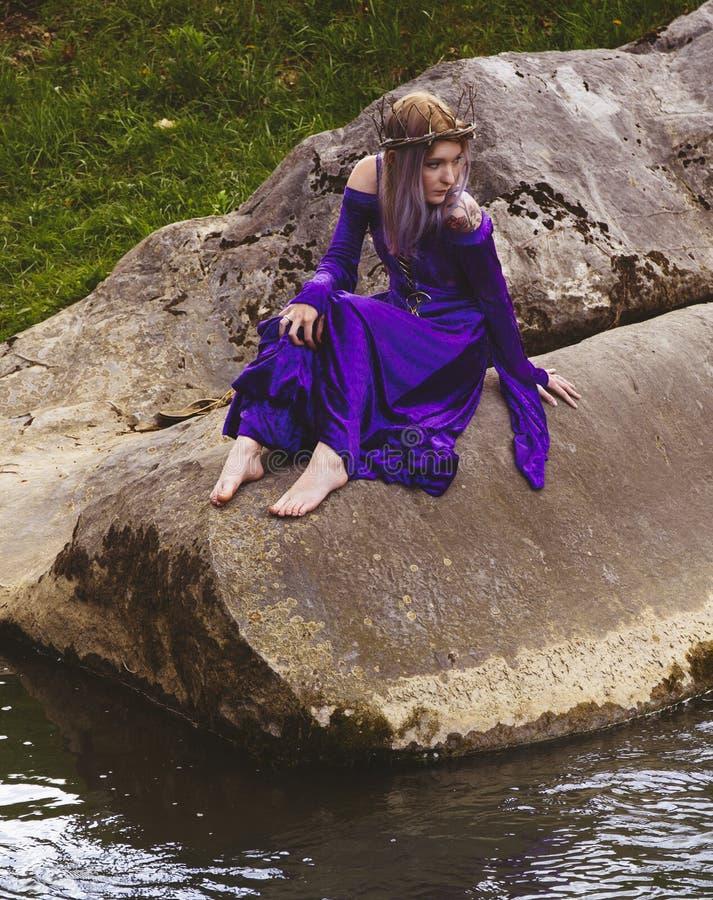 Jonge vrouw in purpere togazitting op rotsen door een rivier stock afbeeldingen