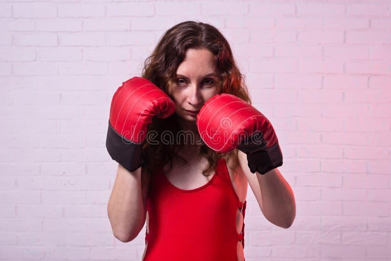 Jonge vrouw in rode bokshandschoenen op een roze achtergrond royalty-vrije stock afbeelding