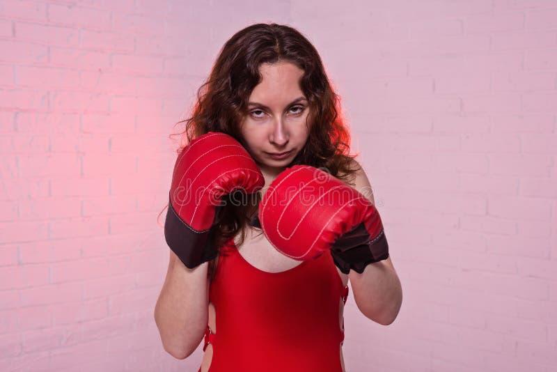 Jonge vrouw in rode bokshandschoenen op een roze achtergrond royalty-vrije stock afbeeldingen