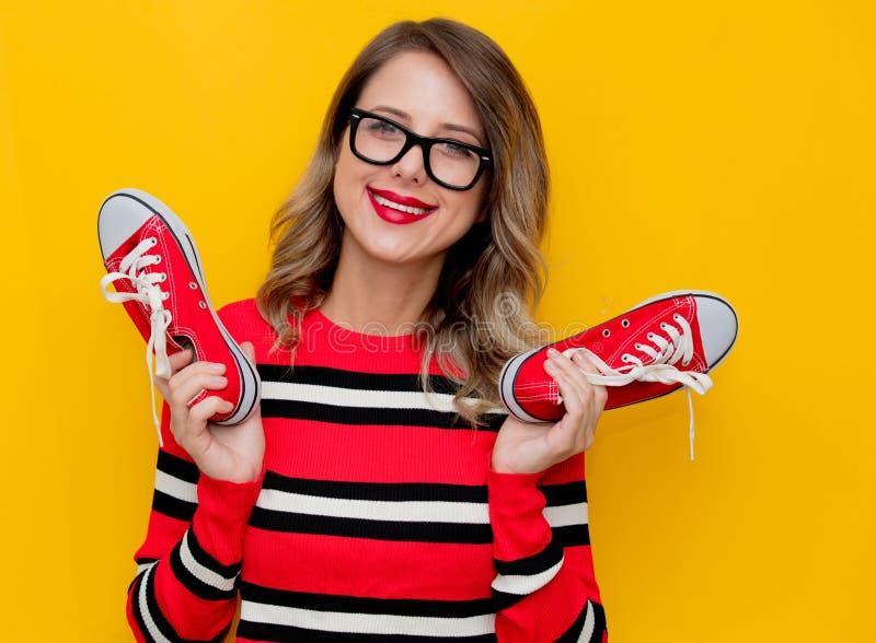 Jonge vrouw in rode gestreepte sweater met gumshoes royalty-vrije stock foto