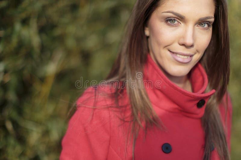 Jonge vrouw in rode laag royalty-vrije stock afbeeldingen