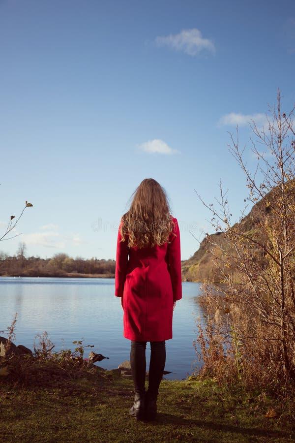 Jonge vrouw in rode laag die weg het kijken over een meer onder ogen zien royalty-vrije stock foto
