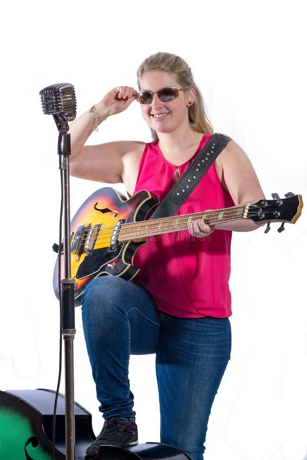 Jonge vrouw in rode T-shirt en jeans die zich voor een microfoon bevinden stock afbeeldingen