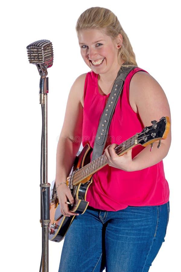 Jonge vrouw in rode T-shirt en jeans die zich voor een microfoon bevinden stock afbeelding